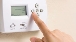 close up of a person's index finger setting a thermostat